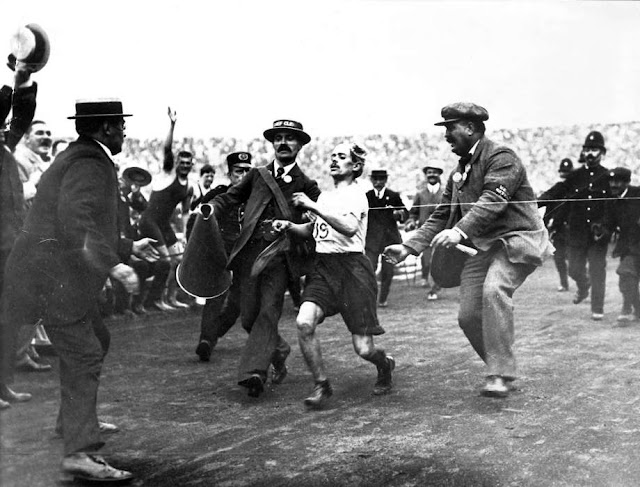 Marathon 1908 London Olympics. Dorando Pietri, dehydrated and disoriented, accompanied by two officials, stumbles across the finish line. Your Russians are missing. marchmatron.com