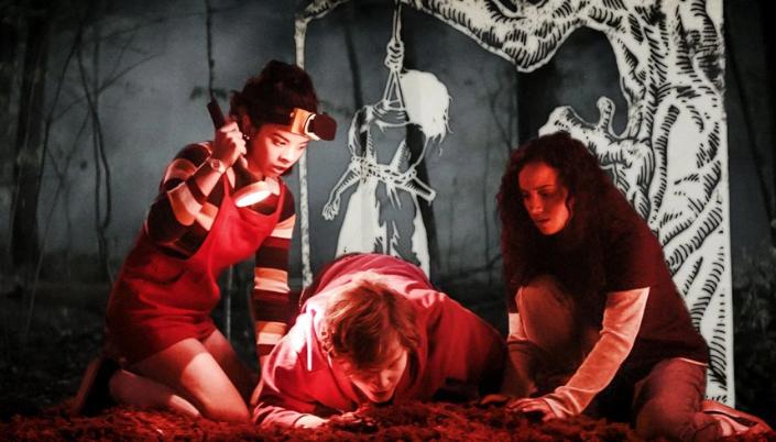 Imagem: os personagens do primeiro filme agachados ao redor de um buraco numa floresta, Kate, em uma blusa colorida e um macacão vermelho, iluminando com uma lanterna, Simon, agachado no chão olhando um buraco e Deena, uma garota de cabelos pretos em uma blusa vermelha por cima de uma blusa de manga longa e branca. E por trás uma ilustração em branco de uma mulher sendo enforcada.
