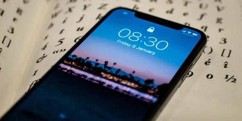 صورة لشاشة قفل جهاز iPhone X مع خلفية صفحة كتاب