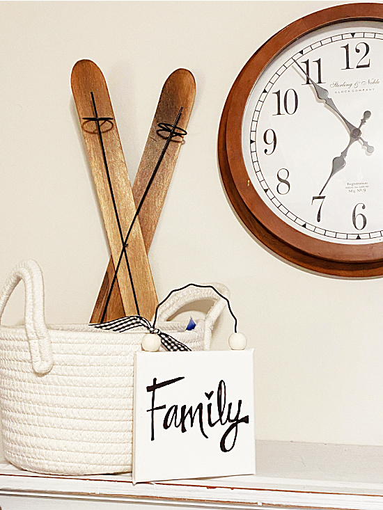 sign on a shelf with skis, a basket and a clock