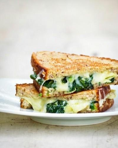 Sandwich panggang berisi artichoke, bayam, dan keju.