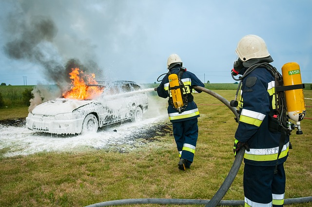 firefighter extinguising a car