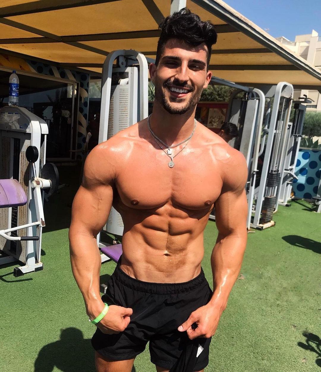 handsome-brazilian-bodybuilder-model-nicholas-gala-smiling-shirtless-shiny-muscular-body-huge-pecs