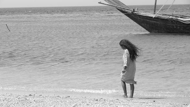 A girl stands by the water