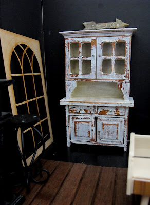 Modern dolls' house miniature room corner with a vintage shabby hutch dresser and wooden gothic window propped against the wall.