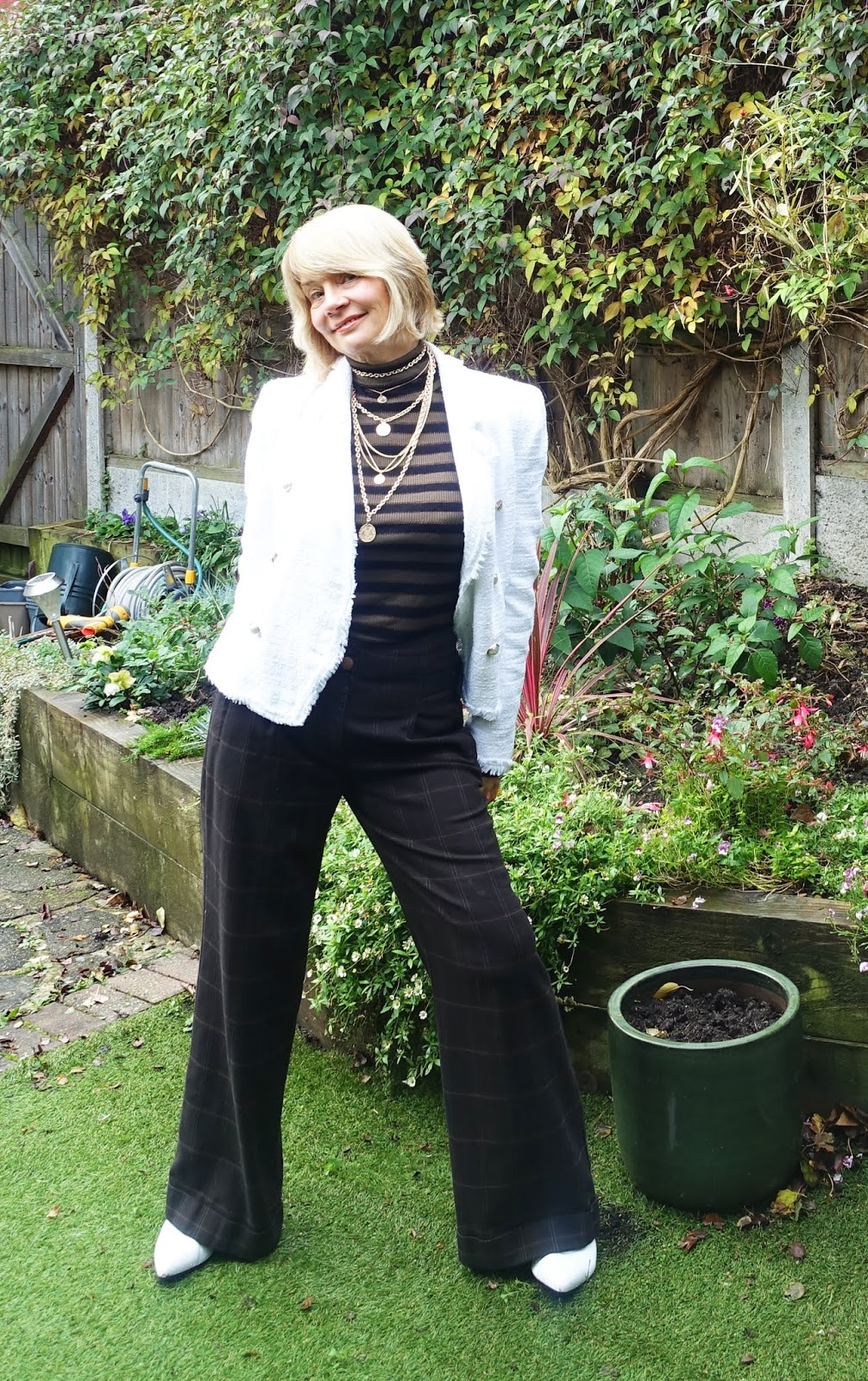 Gail Hanlon from over-50s style blog Is This Mutton takes two trends, mock neck jumper and layered coin necklace, and creates an outfit of brown and white suitable for office to evening wear