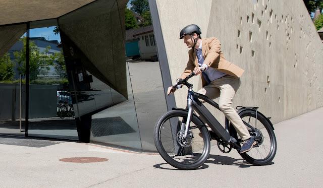 Homem de negócios pedalando bicicleta elétrica