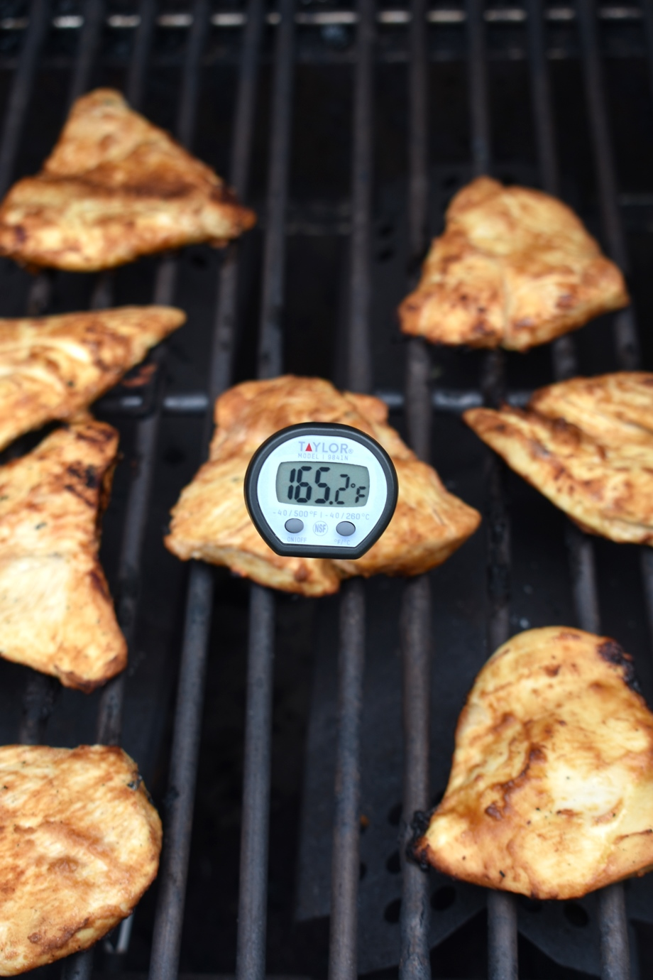 taking temperature of chicken on the grill