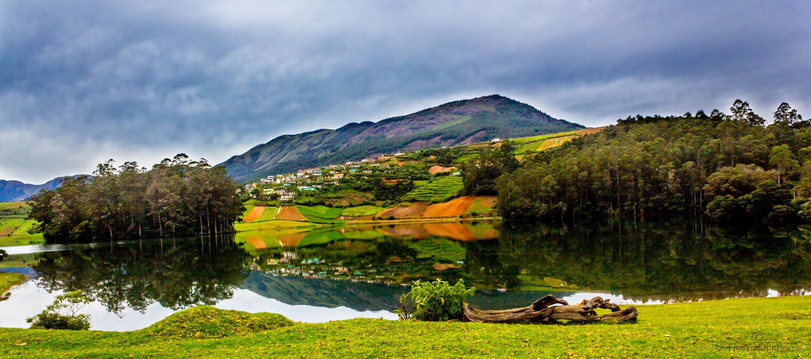 Landscape photo near Avalanche lake Ooty with a mountain in the background and houses on the slope. Lake shore in the foreground.