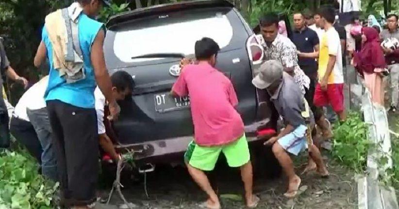 Warga membantu evakuasi minibus yang masuk ke sungai.