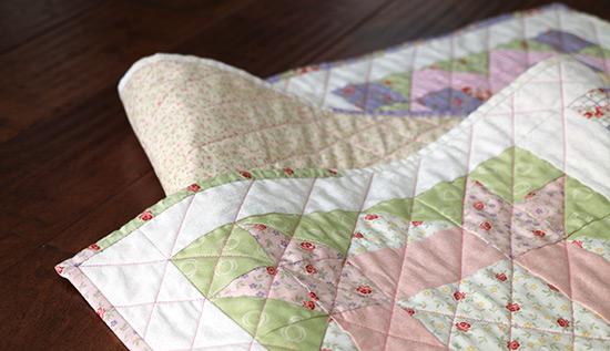 Loosely folded quilted table runner made from pastel floral cotton fabrics, resting on dark wood.