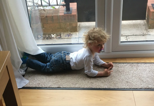 toddler-with-bed-hair-lying-on-floor-in-house