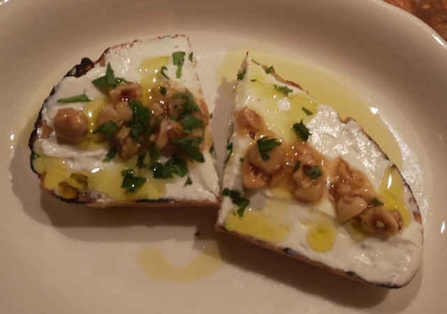 grilled bread covered with goat cheese, honey, pistachios and herbs