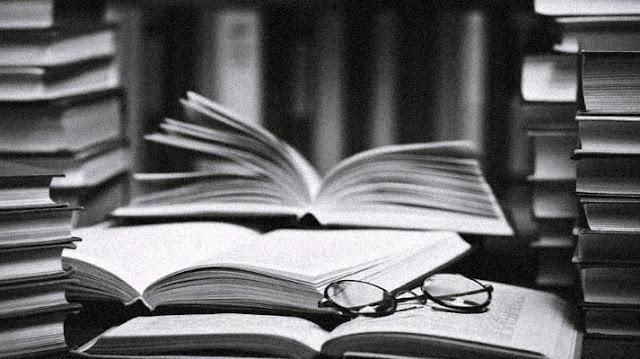 Imagem com pilhas de livros e um óculos, livros que falam sobre epidemias e pandemias, refletindo o momento em que vivemos com o Covid-19