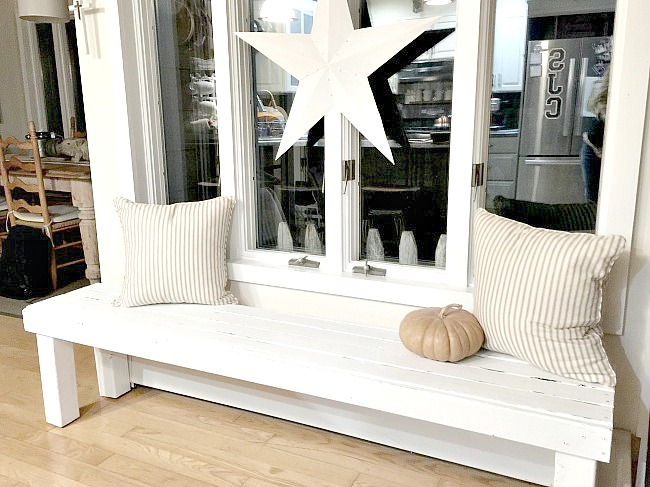White bench under window with pillows