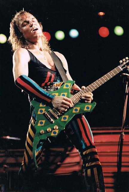 Foto de Matthias Jabs no palco do primeiro Rock in Rio com a icônica guitarra no formato do logo do festival, verde e com bandeirinhas do Brasil.