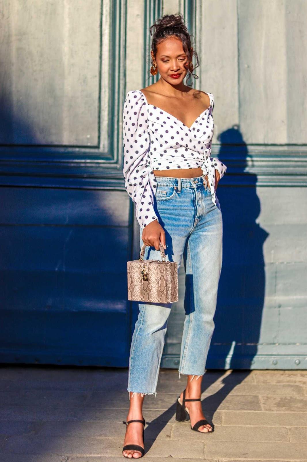 Ayant grandi dans les années 90, j`ai pu avoir une petite aperçue  de l`atmosphère et de l`ambiance   qui régnaient dans les années 80.  Et comment vous dire que j`adore cette époque. C`était la période ou les grandes icones de mode  étaient de femmes d`opinons et de caractère. Entre Naomi Campbell  qui a bousculé le monde de la mode en devenant  la première femme noire  a apparaitre a  la une de vogue France en 1988  ou   Lady Diana  qui  a révolutionné la famille royale d'Angleterre, on est très loin des  stars de télé réalité qui sont devenues les modèles de millions de jeunes filles  aujourd`hui.  On n` était  pas aussi proche de la  course à la perfection  actuelle.  Je n`ai rien contre la technologie, mais imaginez  une seconde si on pouvait  poster sur les réseaux sociaux sans  nous sentir obligé de passer par photoshop, lightroom, VSCO ou d` utiliser des filtres.      Des années 80...une des choses que j`apprécie le plus est sans  doute  la mode. Je pense que  Le monde de la mode n`a jamais connu autant de diversité qu`à cette époque.  Les gens paraissaient plus libre.  Ils s`amusaient avec  les couleurs, les motifs,  les matières,  les volumes, les silhouettes, les accessoires  et  je ne parle même pas des coupes de cheveux.  Vous pouvez visionner  un épisode de la série  Dynastie( l`originale bien sûr)  ou   The cosby show  si vous avez des doutes. Mais à côté de  toutes ces extravagances,  il y avait aussi une élégance qui était propre à cette décennie : L`apparition des premiers blazers pour femmes, les épaulettes XXL, les manches bouffantes,  les boucles d`oreilles  ronde  a clips   ….  Des tendances dont certaines ont   fait leurs grands retours dans les magasins cet été.    Quand j`ai vu cette blouse cache coeur à pois et à manches bouffantes sur le site de  Nastygal, je n`ai pas pu résister.  Il me fait tellement penser à cette ère que j`apprécie  tant.  Aujourd`hui je l`ai porté avec  jean taille haute  à coupe droite acheté chez Zara,  mes  sandale