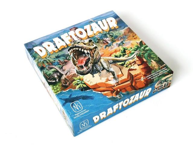 na zdjęciu pudełko gry draftozur a na nim tyranozaur rex z otwarta, ociekającąśsliną paszczą
