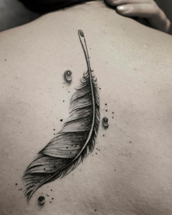 tatuaje de pluma negra espalda femenino