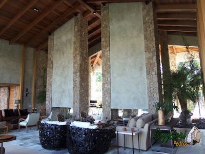 Pilares de pedra, com pedra moledo, na construção da lareira de pedra em sala de estar de residência em Piracaia-SP.