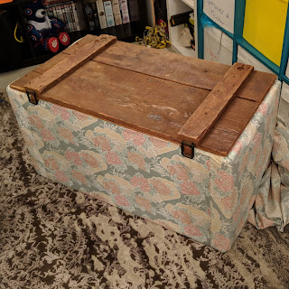 Photo of an ottoman with the lid stripped of fabric, revealing a timber lid with two braces.