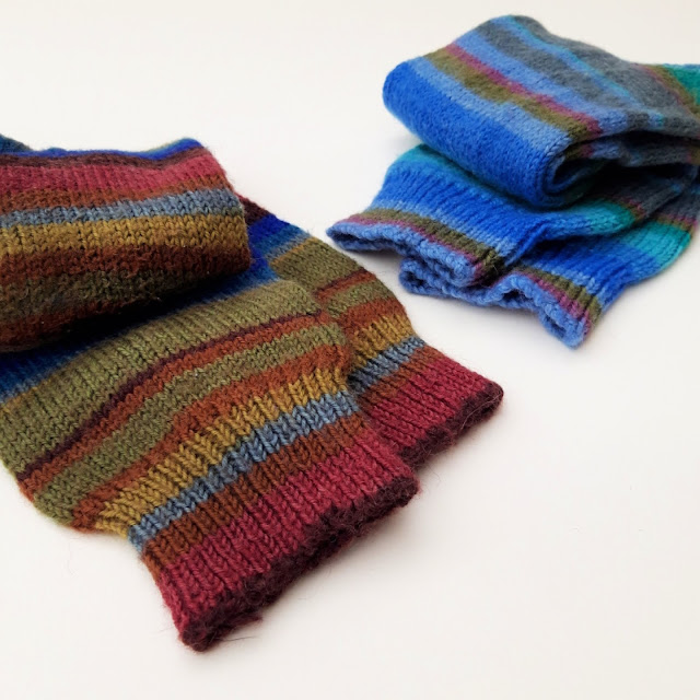 Two pairs of adult socks rolled up against a white background.  The nearest pair is brown and blue stripes, the further pair is blue stripes