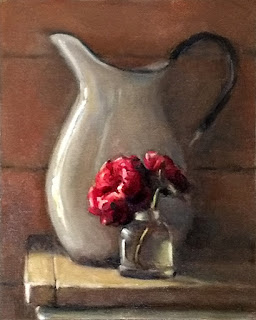 Still life oil painting of crimson roses in a small glass jar beside a white enamelware pitcher.
