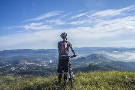 Biker Holding Mountain Bike on Top of Mountain With Green Grass