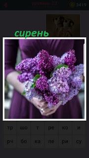 девушка в фиолетовом платье держит букет сирени