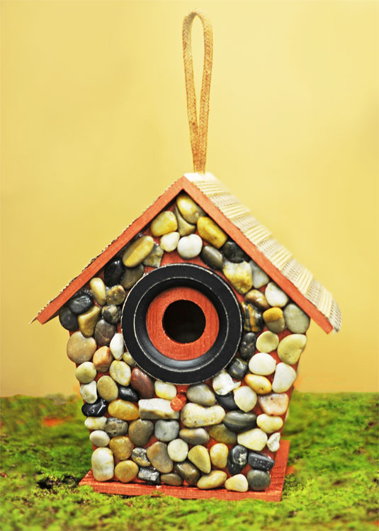 Decorating A Bird House With River Rocks