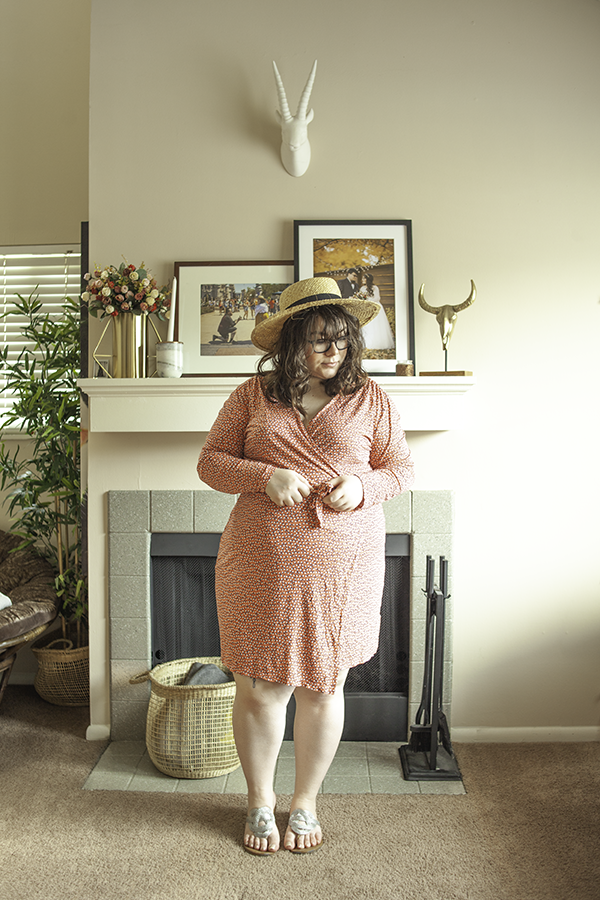 An outfit consisting of a straw sun hat, a coral long sleeve dotted midi wrap dress, and silver knot sandals.