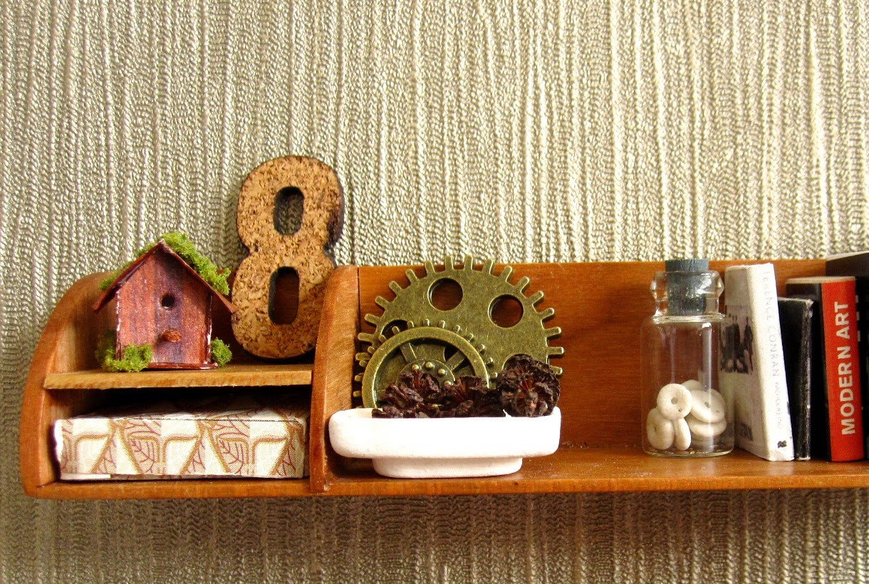 Modern dolls' house shelf  holding a small shabby bird house, a cork number 8, two cogs, a bowl full of pine cones, a jar with shell inside, holding up several books.