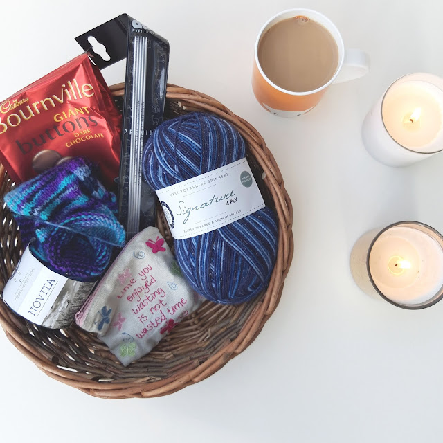 A basket containing some knitting, some dark chocolate buttons, knitting needles and a small notions pouch to the left, and a mug of tea and candles to the right on a white background