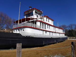 the Sgt. Floyd River Museum and Welcome Center in Sioux City Iowa: a small white steamboat with red trim and black bottom in dry dock sitting in grass, with a wooden walkway leading to the main deck.
