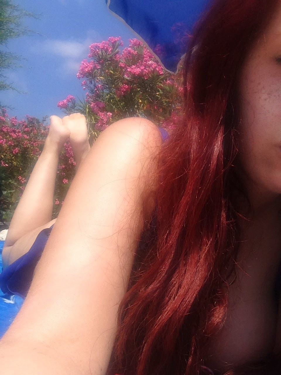 a picture of a girl with bright red hair lounging on a sun lounger, in a bikini