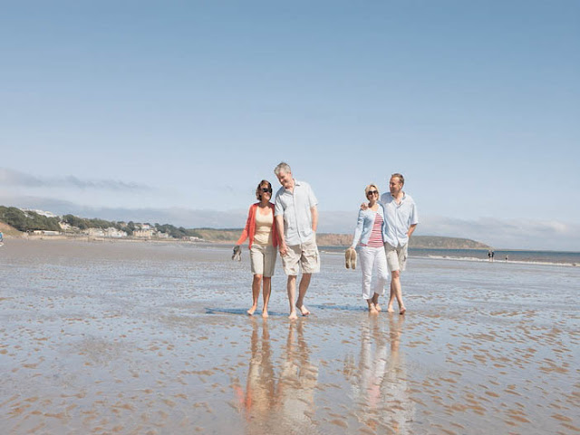 4 adults walking on a beach in Yorkshire
