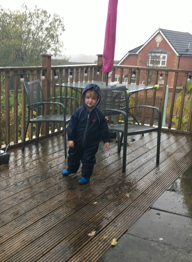 toddler-standing-in-rain-on-decking