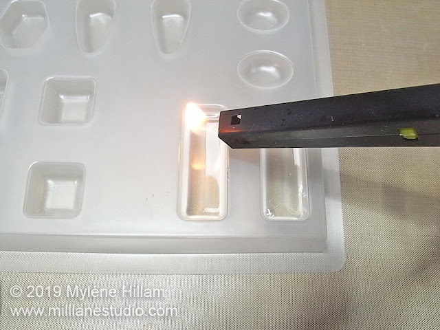 Using a flame to pop the bubbles in the resin.