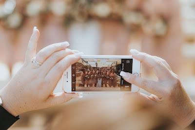 Mujer tomando fotos con un móvil de la novia y sus damas
