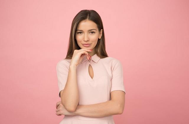 woman looking straight to camera smiling pink background