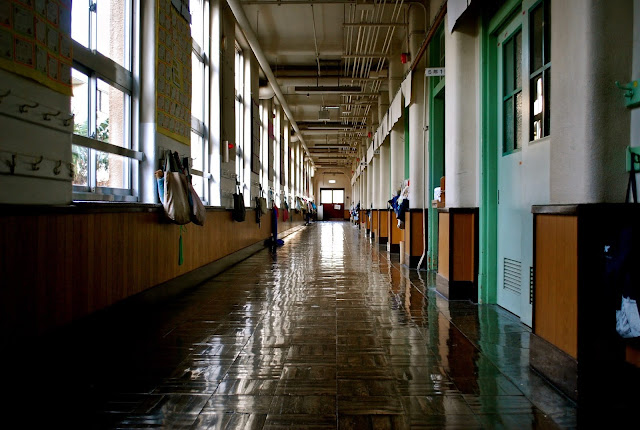 An imposing view of a school corridor, taken from a low angle with a shiny floor and many doors that stretch into the distance.