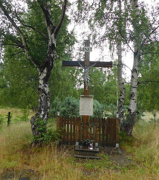 Krzyż przydrożny otoczony brzozami.