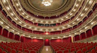 Interior de la sala, en forma de herradura, desde el escenario, Butacas y cortinas de los palcos color rojo  tapizadas en rojo y gran lámpara en el centro