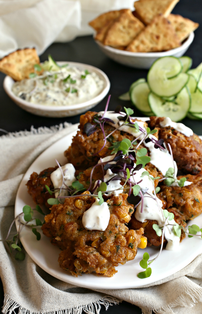 Recipe for savory corn fritters with cheese and herbs, topped with a cucumber yogurt sauce.