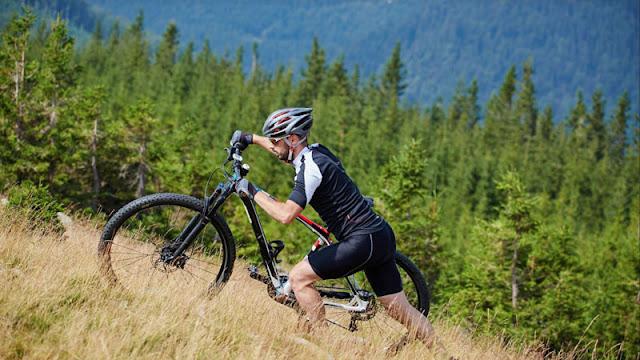 Biker walking bike up hillside