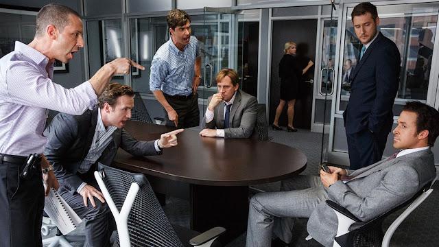Escena de la película con los personajes de Steve Carrel pensativo en la mesa, y Ryan Gosling recostado en su silla