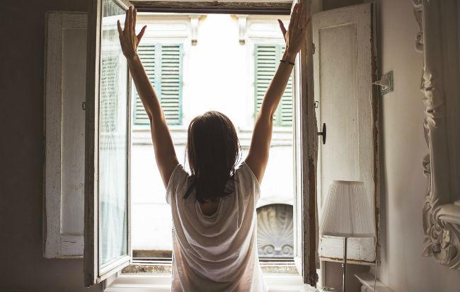 Donna che apre la finestra per arieggiare la casa