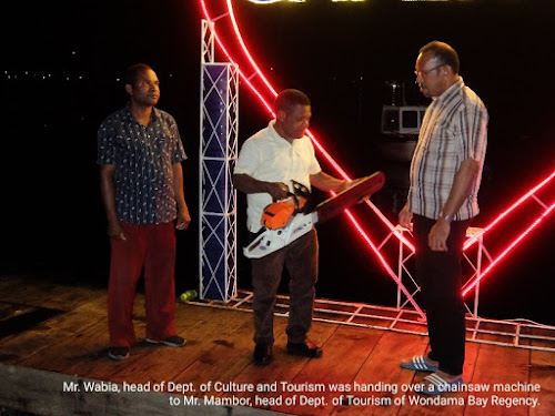 Head of Tourism Department of Papua Barat province handing over a chainsaw machine to head of tourism department of Wondama bay regency