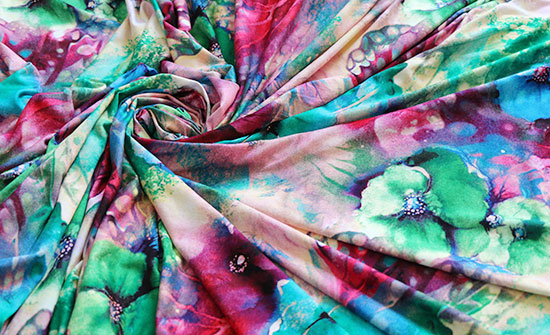 Colorful floral jersey knit fabric arranged in a swirl.