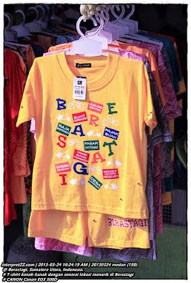 Gambar t-shirt kanak-kanak Beras Tagi berwarna putih yang memaparkan beberapa lokasi pelancongan seperti Gunung Sibayak, Bukit Gundaling, Raja Berneh, Pajak Buah, Pasar Hitam, Taman Bunga Tongkoh, Gunung Sinabung, Desa Lingga, dan Mickey Holiday Resort.